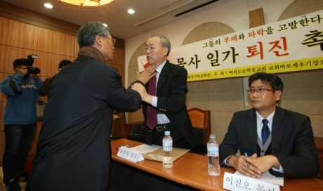 A supporter of Yoido Full Gospel Church senior pastor David Yonggi Cho reaches for the throat of former church elder Ha Sang-ok in a confrontation during a press conference by a group of 30 elders calling for Cho and his family to leave the church amid allegations of corruption, held at the Korea Ecumenical Building in Seoul's Jongno district, Nov. 14. (by Kim Bong-gyu, staff photographer)