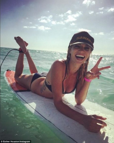 Surfing missionary: Esther pulls a peace sign while wearing a Hawaii cap in the ocean