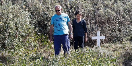 Gordon Davis and his granddaughter, Alana, visit a memorial cross for Davis' stepdaughter, Lynette Daley, on Ten Mile Beach near Yamba, Australia.